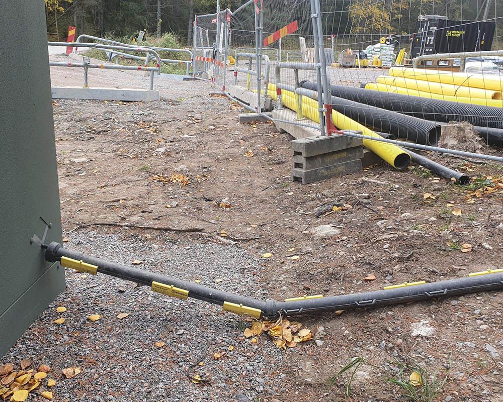Delbart kabelskyddsrör skyddar tillfälliga kablar vid byggarbetsplats i Stockholm.